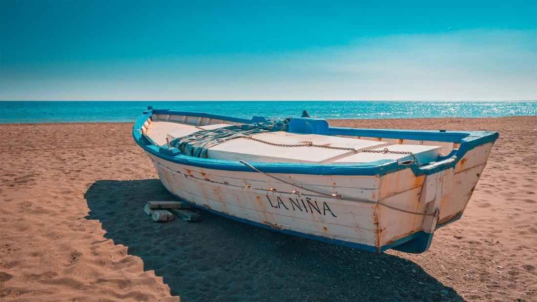 beach blue sky boat calm