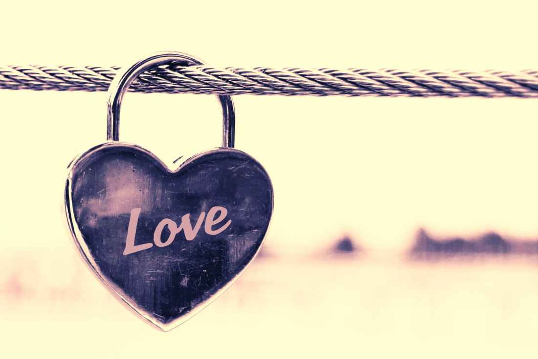 close up of padlocks hanging on heart shape