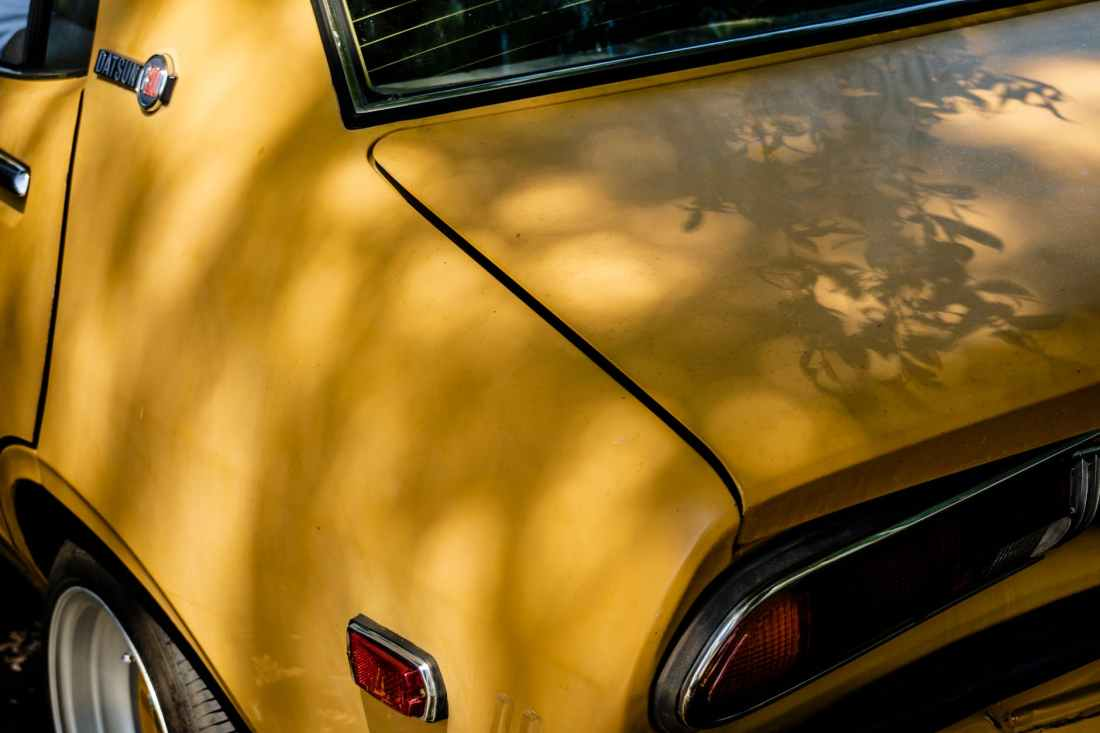 yellow classic datsun car